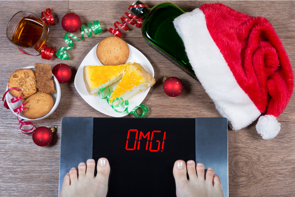 female feet on digital scale surrounded by christmas food and decorations
