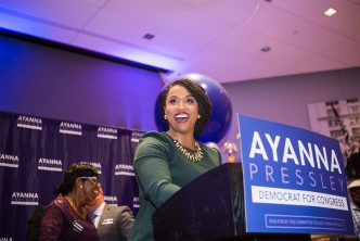 Ayanna Pressley smiles at the podium while speaking to a crowd on her victory election night party.