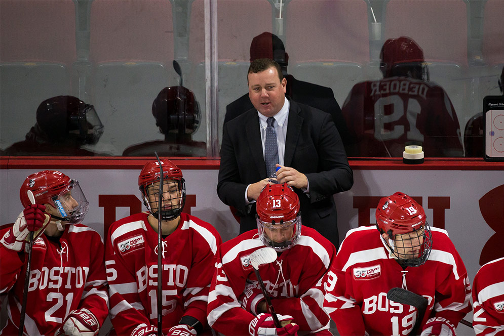 BU men's ice hockey head coach Albie O'Connell talks to a player on the bench during a game.