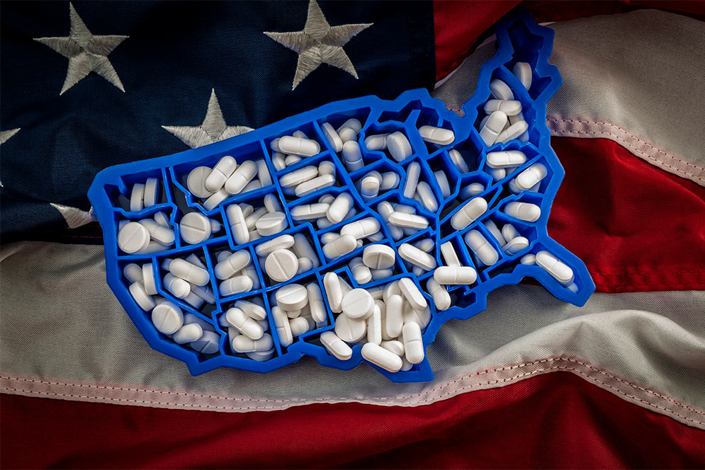 Concept photo of a United States shaped pill box holding a lot of pills resting on an American flag, symbolizing the opioid crisi in America