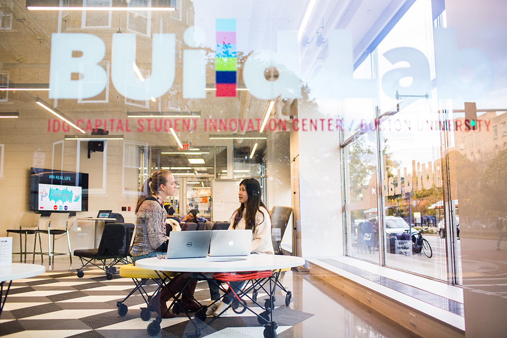 A BU student works with her Hub cocurricular supervisor, seen through the window of the BUildLab: IDG Capital Student Innovation Center at Boston University.