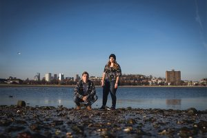 Portrait of Jacob Jaskiel, kneeling, and Hayley Goss, standing, on a Boston Harbor beach with the Boston skyline in the background.