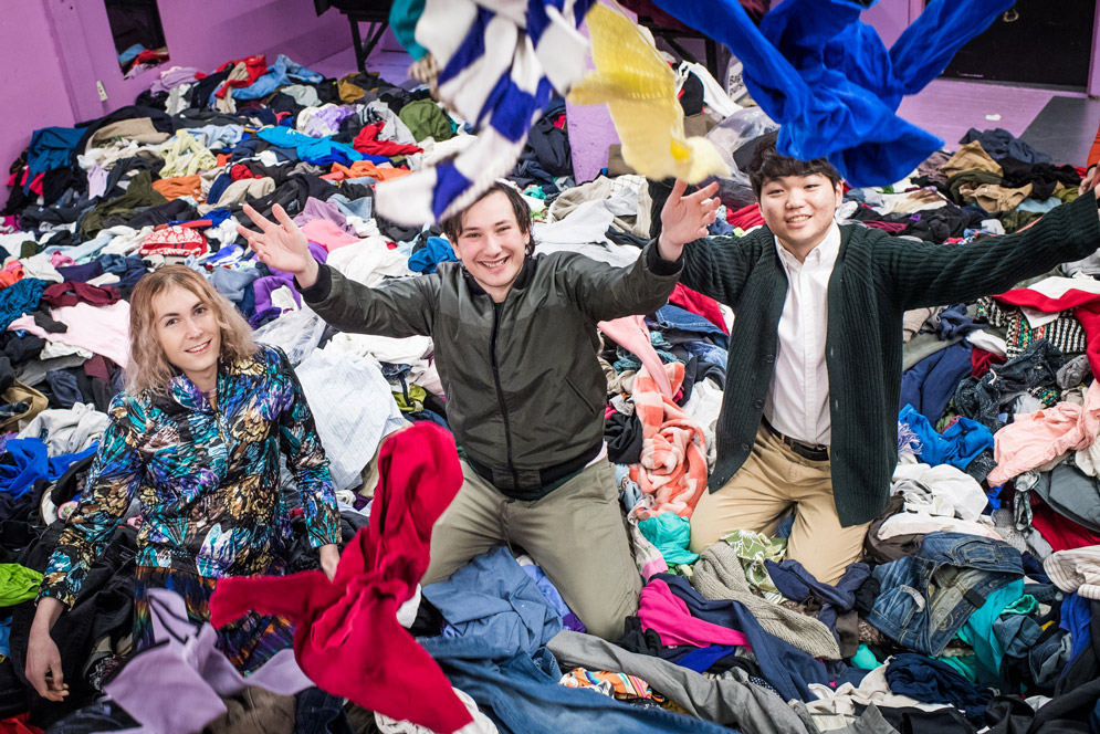 Students playfully toss cloths at the camera in the garment district