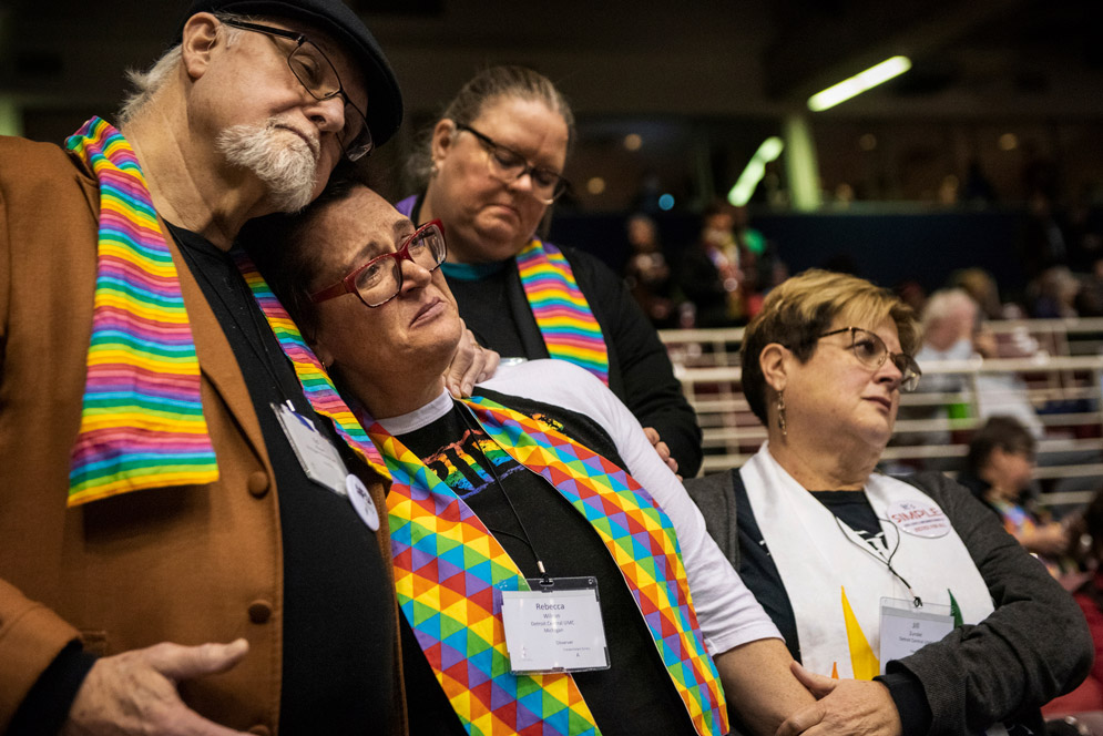 Pro-LGBTQ Methodists comfort each other after the Methodist Church delegates stiffened rules against LGBT clergy and same-sex marriage