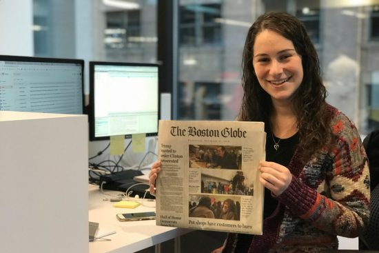 Felicia Gans holds up a paper copy of the Boston Globe