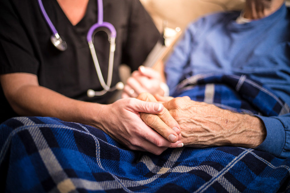 A caregiver holds an elderly person's hands