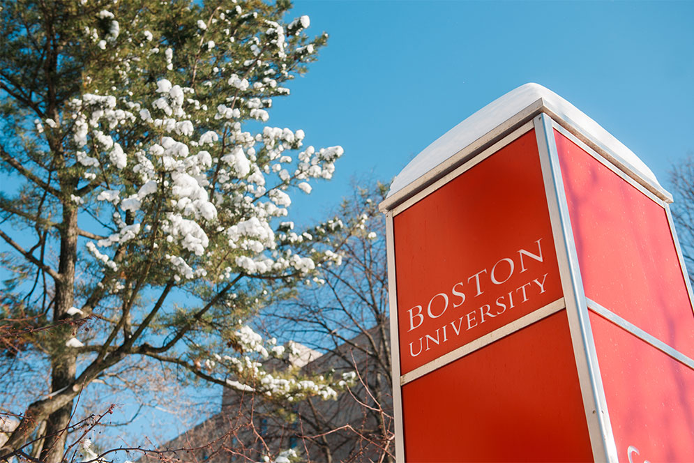 Boston University sign with snow on top in front of a snowcovered tree