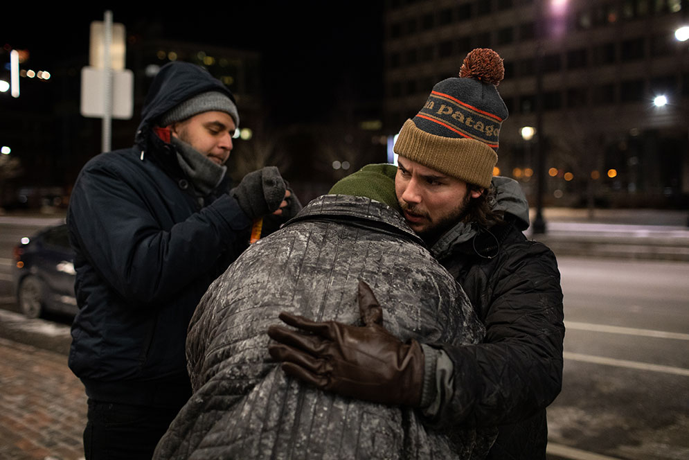 A City of Boston volunteer hugs a homeless person during the annual Boston Homeless Census.