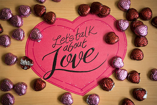 "Paper valentine greeting that says ""Let's Talk About Love"" surrounded by chocolate hearts."