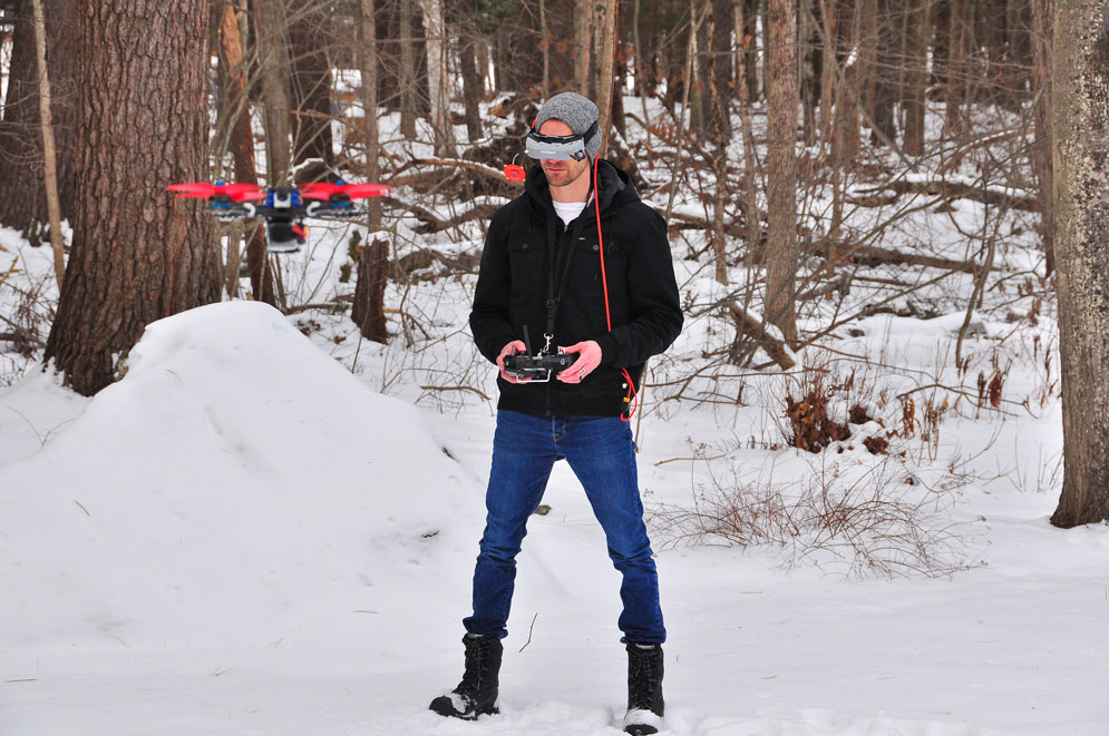 First-person-view droning is a technique where a person wears a headset connected to a video feed streaming live from a camera on the drone. Wil Koch, pictured here, uses the technique to operate a drone outfitted with a Neuroflight controller, which uses a trained neural network to maneuver through dynamic environmental conditions like wind. Courtesy of Wil Koch