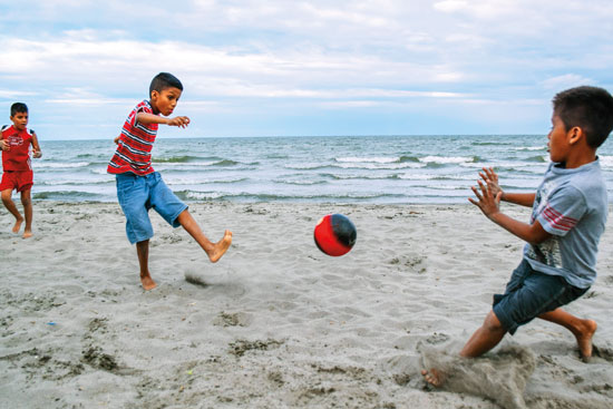 two kids playing soccer on the beach