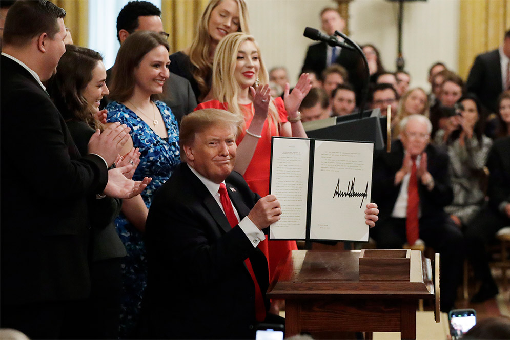 President Donald Trump holds up an executive order on campus free speech, surrounded by college students.