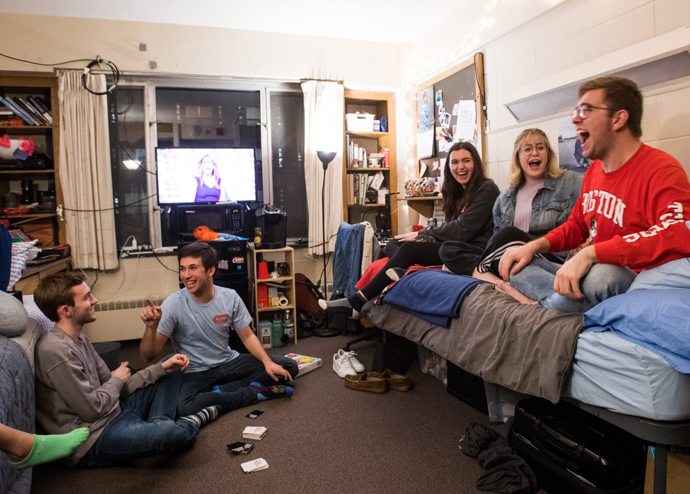 Students laugh while they play cards in a dorm room