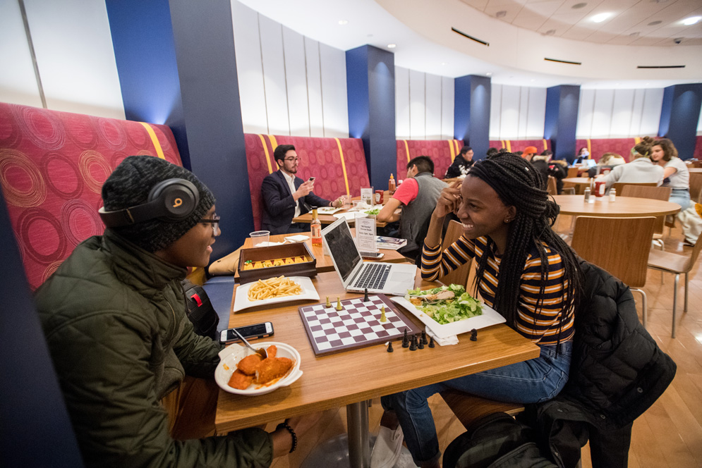 Two students, who are dating, play chess together at Bay State Underground