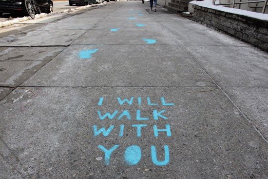 the sidewalk, with I WILL WALK WITH YOU and footprints painted on it in blue