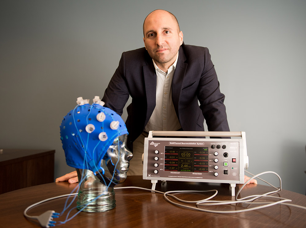 Portrait of Rob Reinhart, assistant professor of psychological and brain sciences at Boston University, posing with an electrstimulation device that he uses in his research.