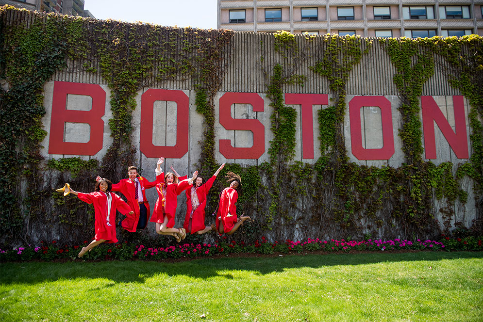 5 members of Boston University Class of 2019 wearing their red graduation robes jump in the air in front of the word Boston on Nickerson Field