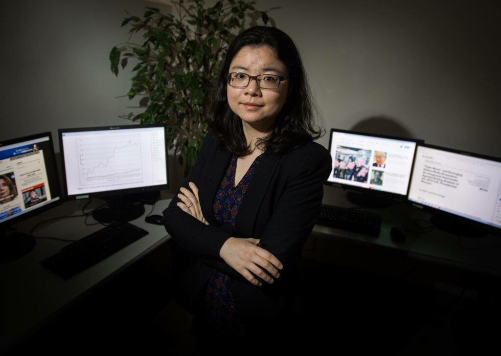Lei Guo, a COM assistant professor of emerging media studies, poses in front of four desktop screens.