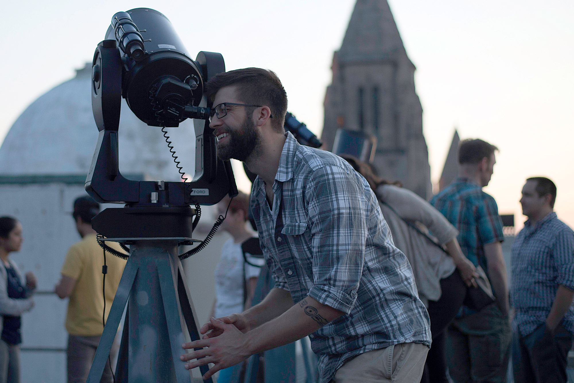 A student peers through a telescope at the Boston University Coit Observatory.