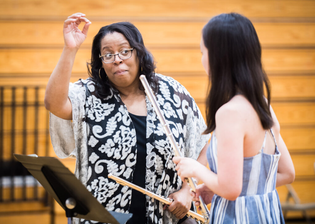 Coleman instructs a student playing the flute