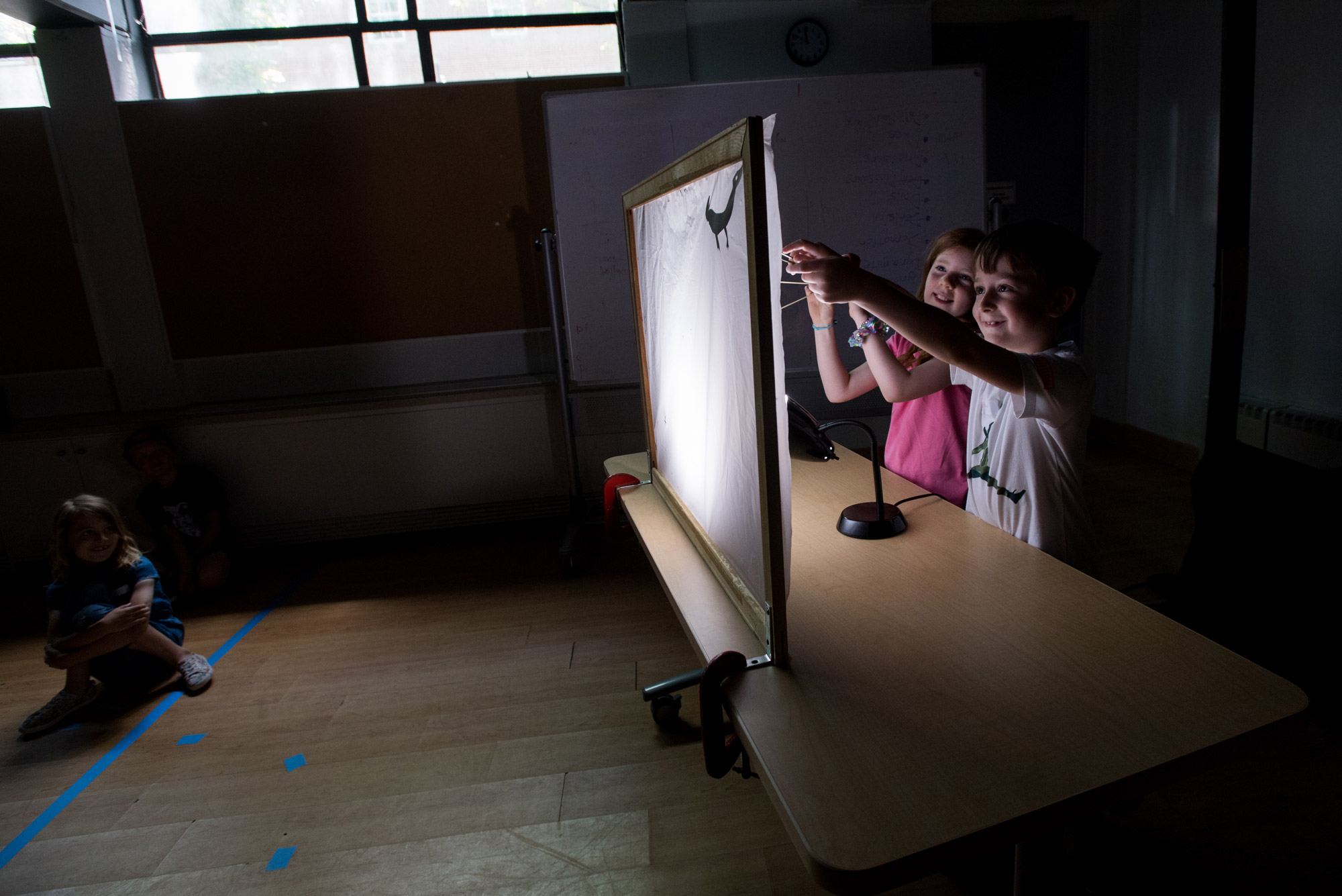 Two children play with shadow puppets
