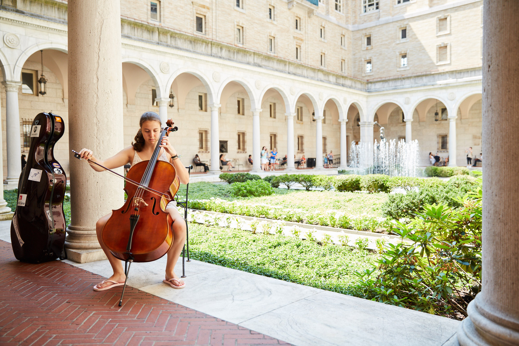 A woman plays the cello in the courtyard at the Boston Public Library during a free concert