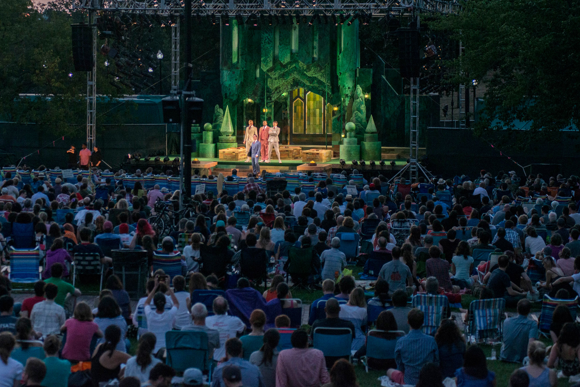 a crowd watches the Last year Commonwealth Shakespeare Company perform onstage