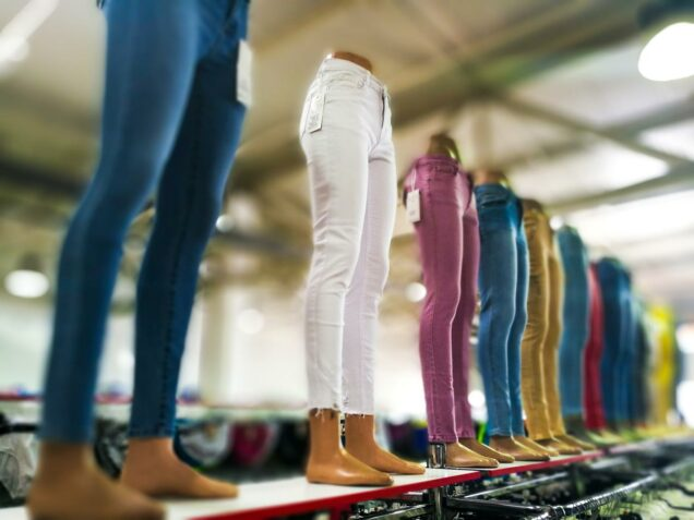 A row of manequin legs display women's skinny jeans in a clothing store.