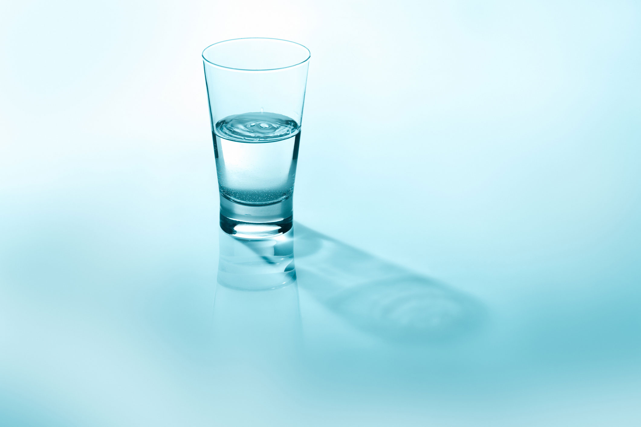 Glass of water, half full, against a light blue background.