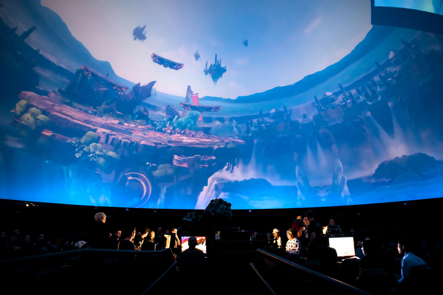 View from within the Omni Theatre in Boston's Museum of Science. A preview of gamers on their laptops in the theatre playing overwatch live on the dome screen above them.