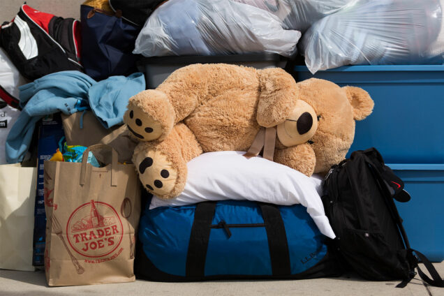 Moving bins, trashbags, duffle bags and stuffed teddy bear sit on a sidewalk outside Boston University dorms during Fall semester student move-in.