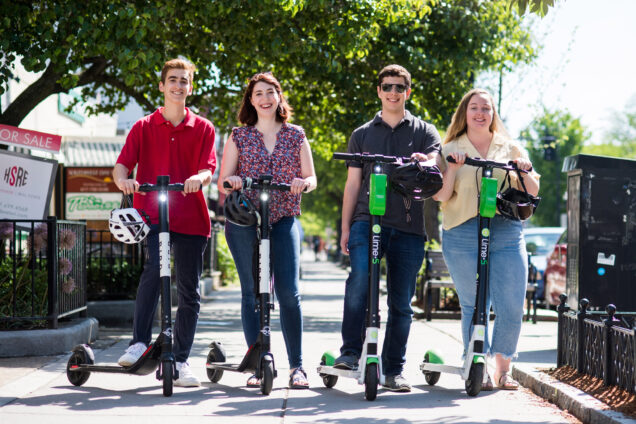 BU Today summer interns pose with Bird and Lime scooters