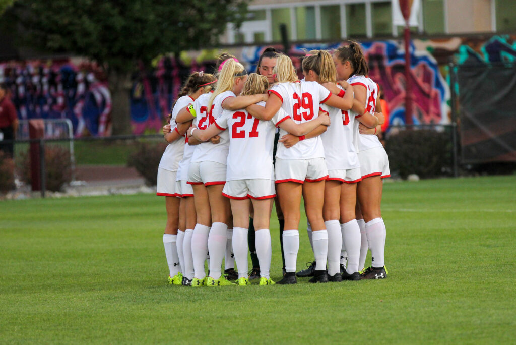 The Boston University Women's team huddles on the field during a game.