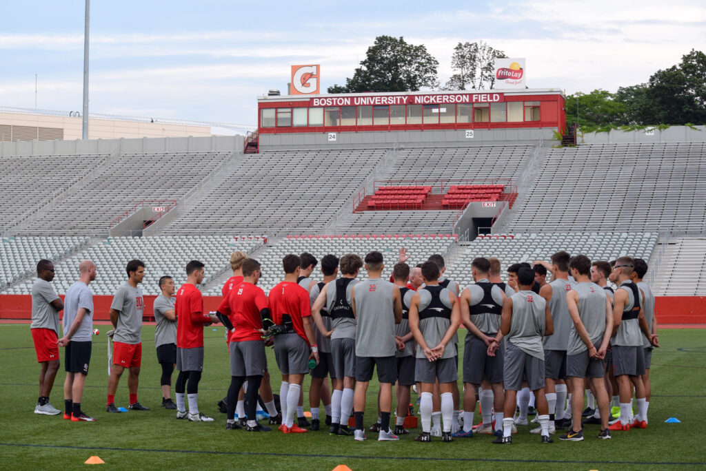 The Boston University men's soccer team gathers on the field during a preseason practice.