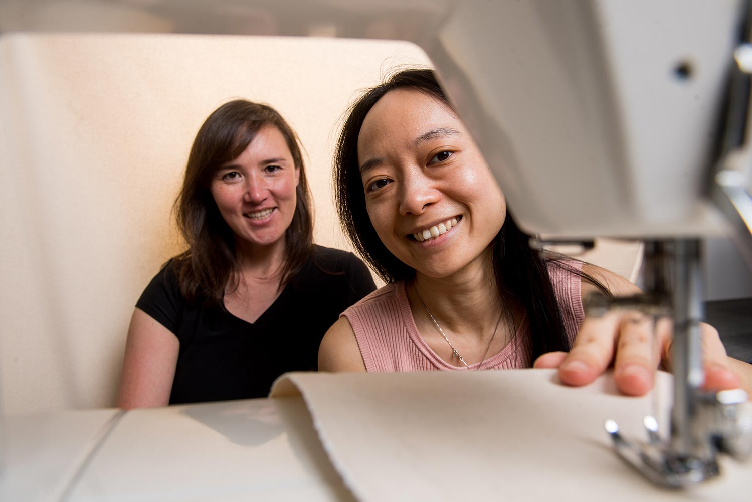 Boston University computer science researchers Emily Whiting and Xiaoting Zhang pose for a portrait behind a sewing machine.