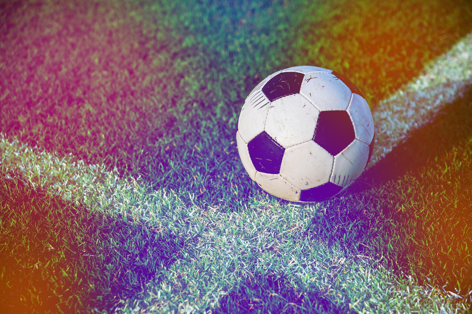 Soccer ball resting on a soccer field line with rainbow color overlay.