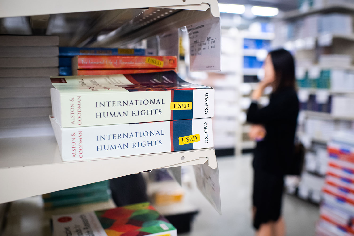 Two used copies of an International Human Rights textbook on a shelf with a customer browsing textbooks in the background