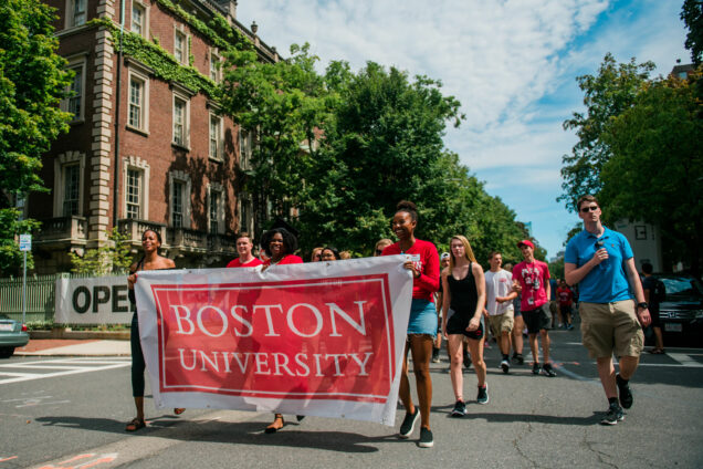 Three African American women carry a Boston University banner leading the Class of 2023 Matriculation parade.