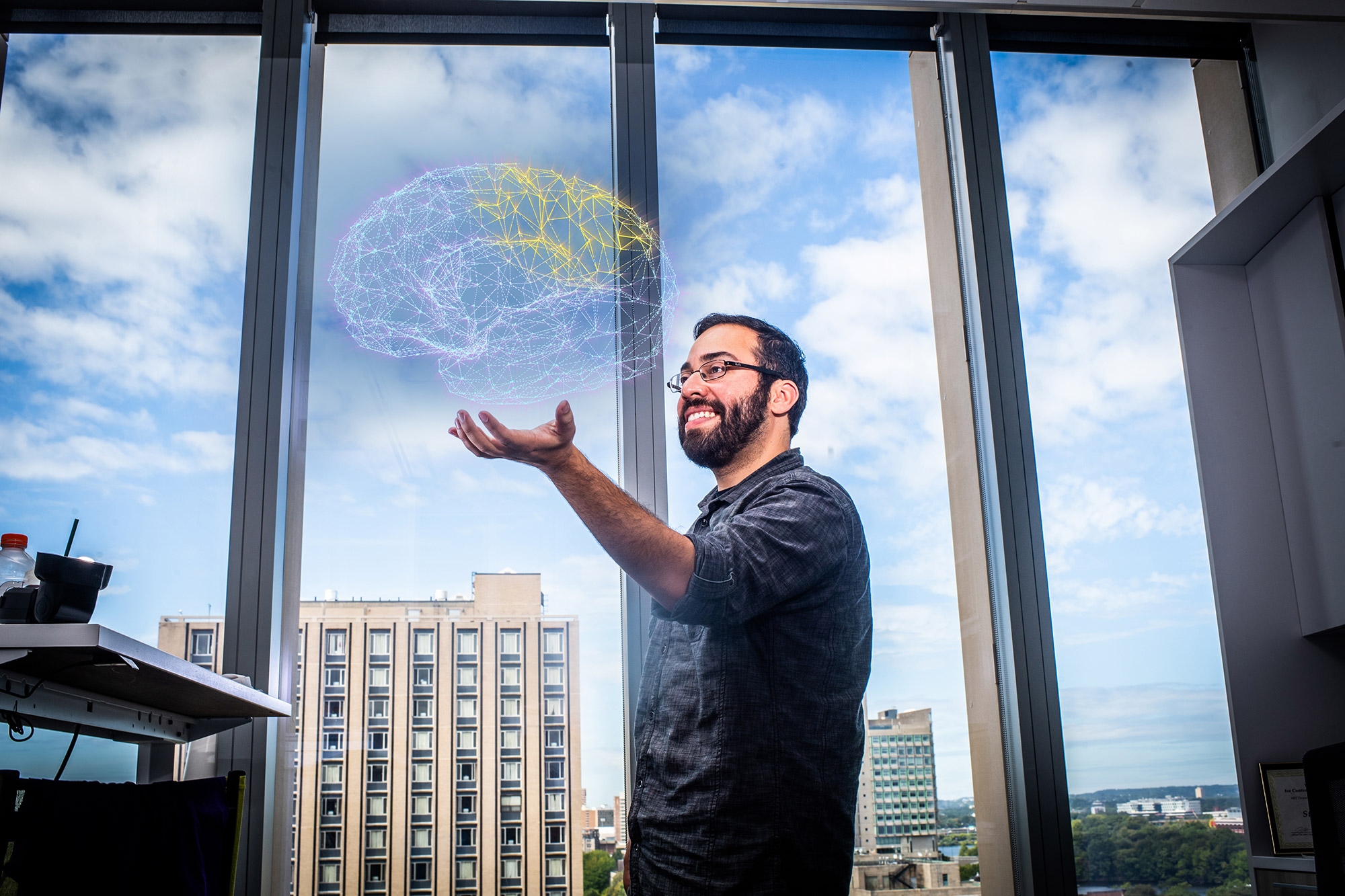 Neuroscience researcher Steve Ramirez holds a digital diagram of a brain.