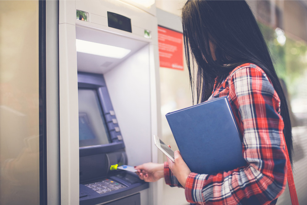 A woman withdraws cash from an ATM