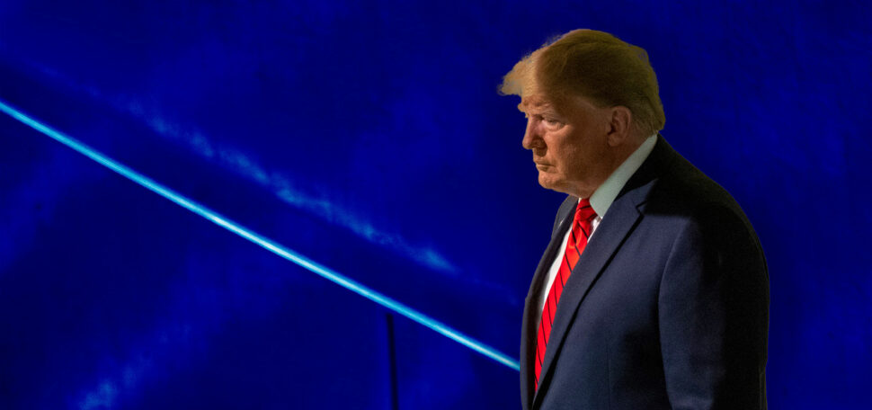 Donald Trump looking pensive in front of a textured blue background.