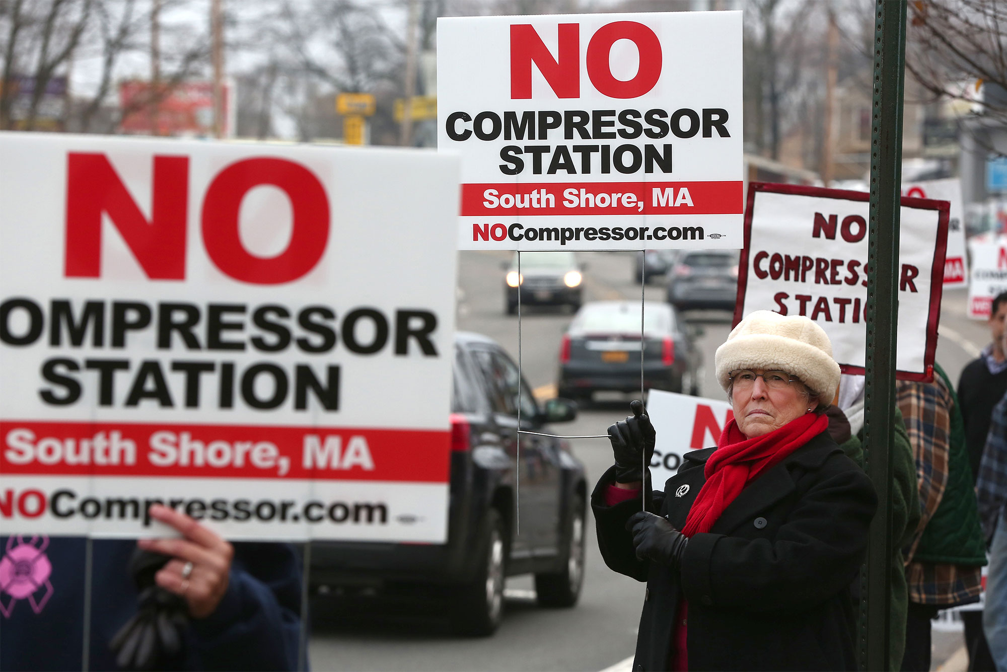 People hold signs protesting a proposed natural gas compressor station in Weymouth, Massachusetts.