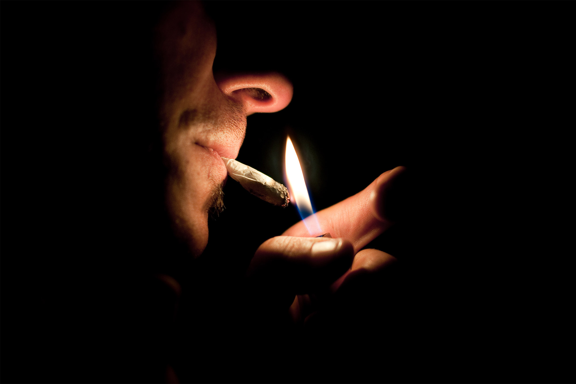 a man lights a joint with a lighter in the dark.