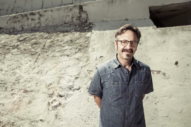 Portrait of Marc Maron standing in a dry waterway