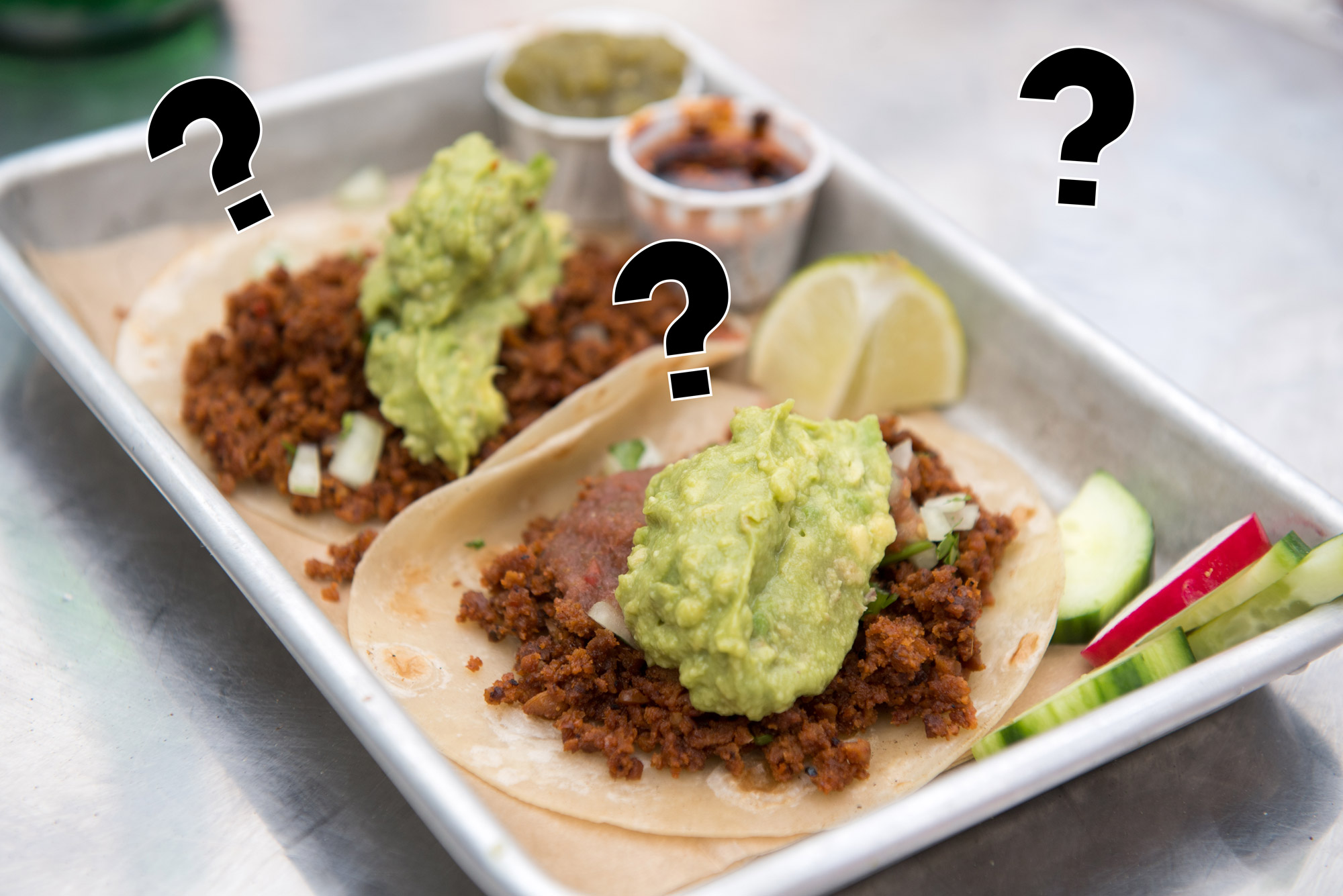 A picture of vegan chorizo tacos with question marks hanging above it