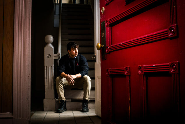 A Boston University student poses in the doorway of his new off-campus apartment in Allston.