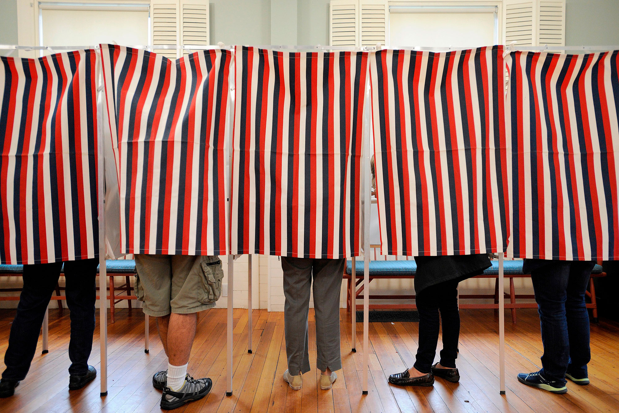 Voters stand behind red, white, and blue striped separators
