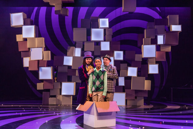 Ricky Holguin (left) as Willy Wonka, Jamie Leslie as Charlie Bucket, and Neil A. Casey as Grandpa Joe in Wheelock Family Theatre's production of Roald Dahl's Willy Wonka