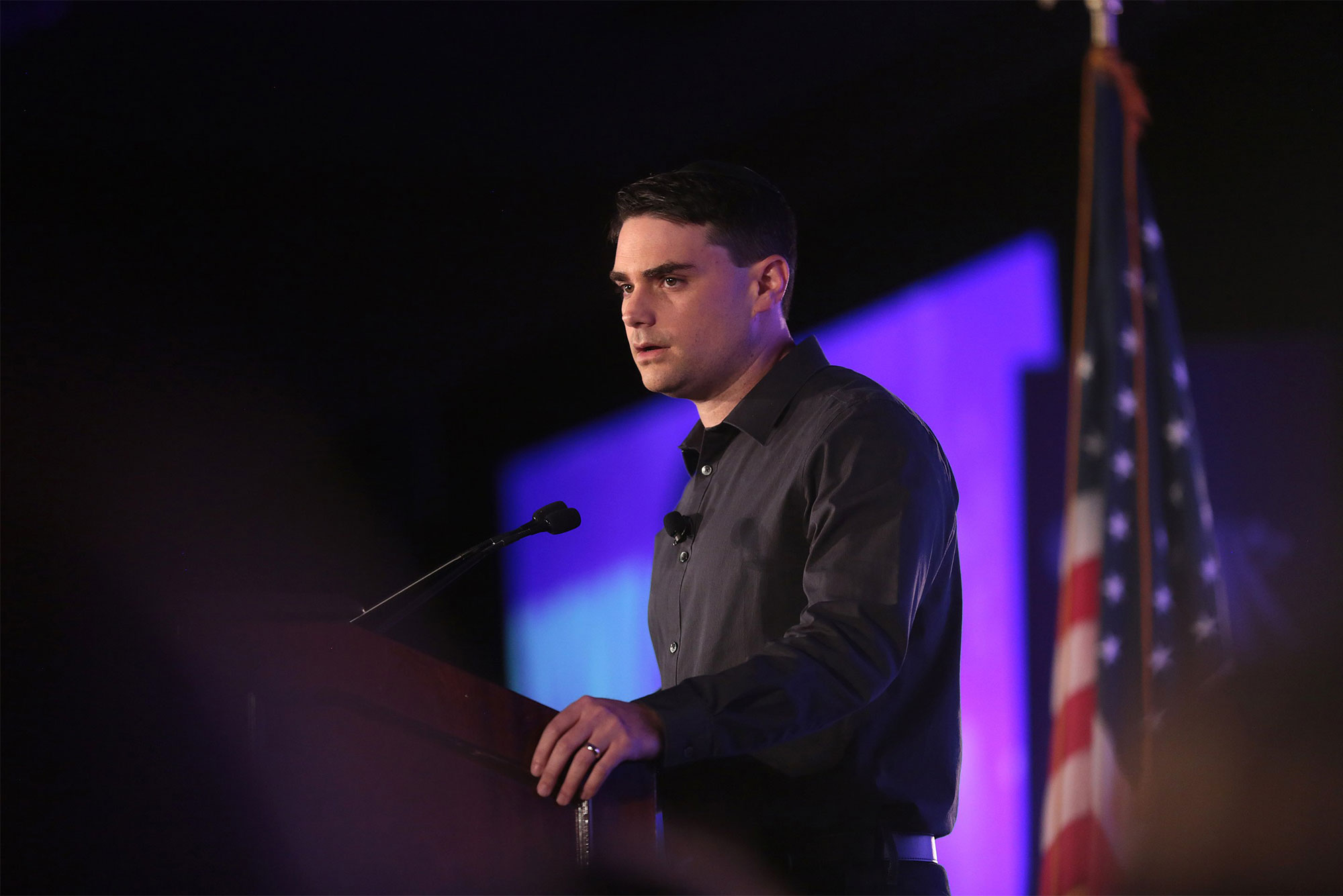 Conservative commentator Ben Shapiro speaking at a podium during a public appearance.