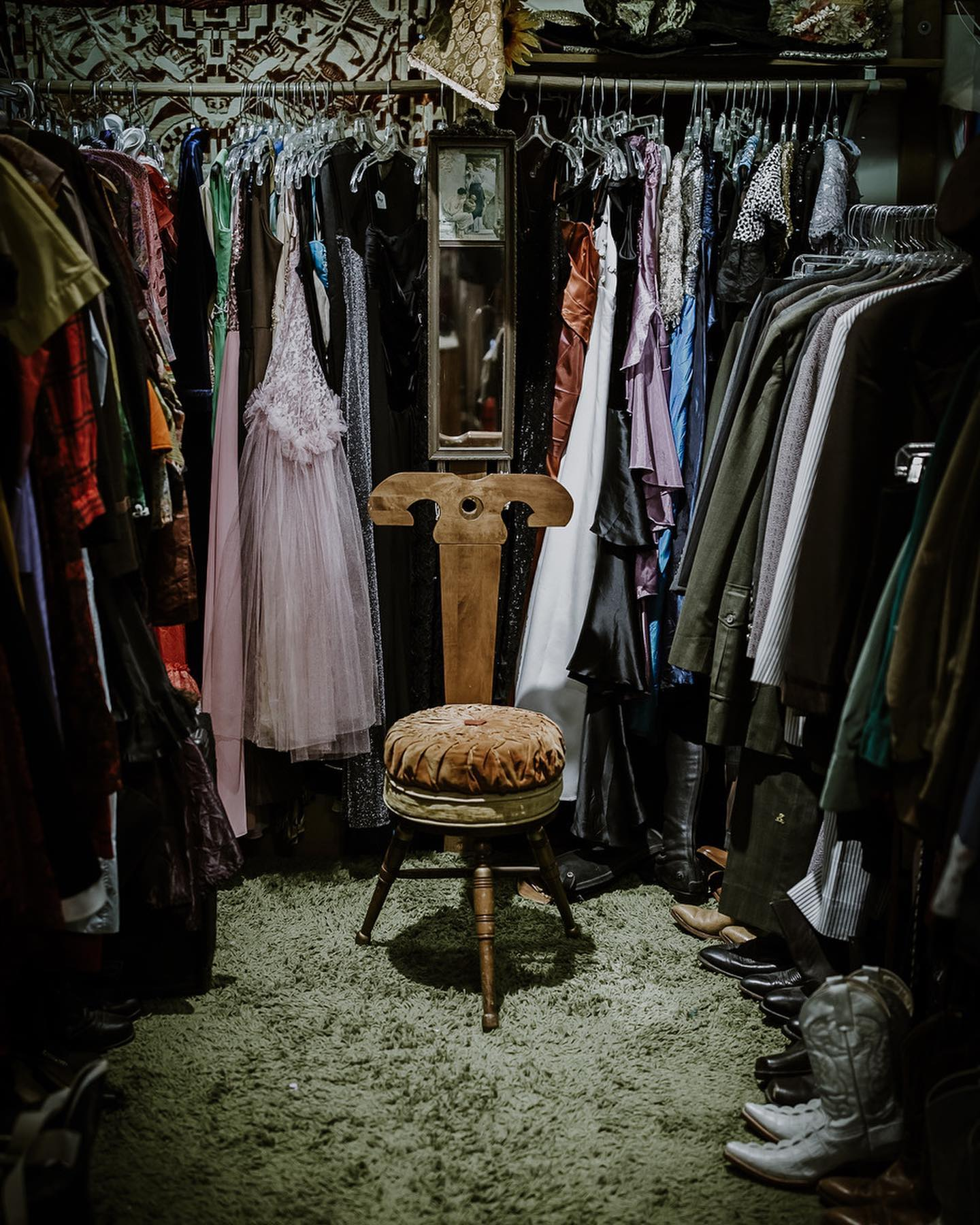A unique chair is surrounded by hanging clothes in the Great Eastern Trading Co.